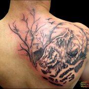 קעקוע של זאב עם שקיעה ועצים על השכם