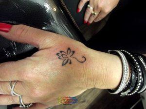 קעקוע פרח עדין בשחור לבן על גב כף היד